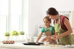 在厨房里照顾和她的女儿用曲奇饼面团 库存照片