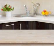 在厨房龙头内部背景的木桌 免版税库存图片