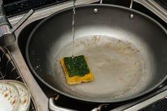 在厨房水槽的一个肮脏的平底锅 库存照片