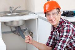 在厨房水槽附近的微笑的水管工 免版税库存图片