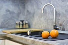 在厨房worktop的桔子对水槽 图库摄影