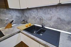 在厨房worktop的桔子对水槽 库存图片
