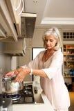 在厨灶上面的老妇人开水 免版税库存照片
