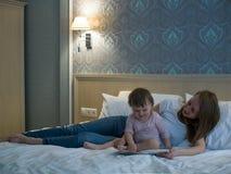 在去前睡照顾读书婴孩在床上 免版税库存图片