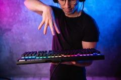 在去游戏玩家的手上的特写镜头按在键盘的一个键 背景是与霓虹灯的升 免版税库存照片
