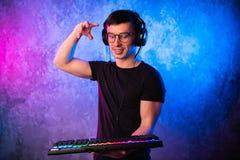 在去游戏玩家的手上的特写镜头按在键盘的一个键 背景是与霓虹灯的升 免版税图库摄影