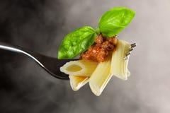 在叉子的新鲜的煮熟的面团用博洛涅塞调味汁和绿色蓬蒿 免版税库存照片