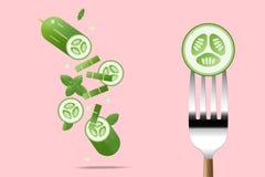 在叉子的新鲜的黄瓜有飞行黄瓜背景,健康食物概念 库存图片