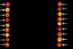 在叉子的蕃茄在黑背景 免版税库存照片