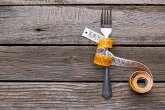 在叉子附近被包裹的测量的磁带 概念饮食 免版税库存图片