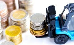 在叉架起货车堆积的金黄和银币 免版税库存照片
