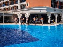 在友好的马球比赛前的片刻在五星旅馆的蓝色水池 库存图片