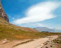 在双突透镜的云彩下的暗藏的湖供徒步旅行的小道在摇石通行证在2017秋天火期间的冰川国家公园在蒙大拿美国 库存图片