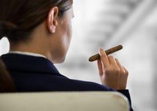 在反对模糊的灰色台阶的肩膀女商人抽烟的雪茄 库存照片