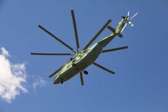在反对白色云彩的天空飞行在camo绘的世界26光晕的最大和装载举的直升机, t 图库摄影