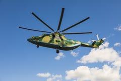 在反对白色云彩的天空飞行在camoufl绘的世界26光晕的最大和装载举的直升机 免版税图库摄影