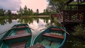 在反射五颜六色的天空的池塘的小船 免版税图库摄影