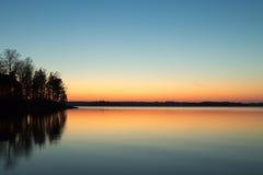 在反射在有春天日落的湖的点的客舱 免版税库存照片