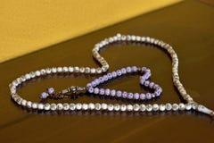 在反射性背景隔绝的心脏形状的伊斯兰教的念珠迷迭香 库存照片