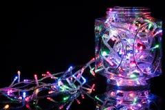 在反射性黑背景的圣诞灯 假日发光的诗歌选边界 图库摄影