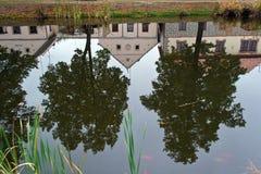 在反射池塘的表面上的农村房子之间的树 免版税库存图片