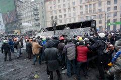在反政府抗议Euromaidan期间,在被翻转的占领街道上的恼怒的人群烧光在demostration的公共汽车 免版税图库摄影