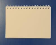 在发光的书桌上的葡萄酒空白的笔记本 库存图片