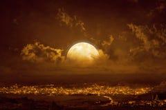 在发光的天空的上升的黄色红色满月 免版税图库摄影