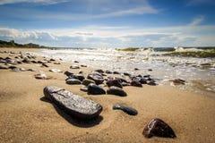 在发光的海滩的小卵石在阳光下 免版税库存照片