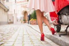 在发光的红色moto滑行车旁边的时髦和端庄的妇女 免版税图库摄影