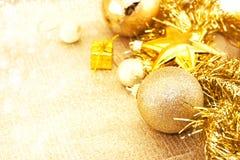 在发光的背景的金黄圣诞节装饰与拷贝空间 图库摄影
