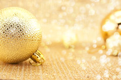 在发光的背景的金黄圣诞节装饰与拷贝空间 免版税库存图片