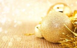 在发光的背景的金黄圣诞节装饰与拷贝空间 免版税库存照片