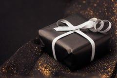 在发光的背景的黑礼物盒 库存照片