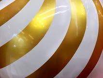 在发光的金黄球形的白色螺旋条纹图形室内装璜的 免版税库存图片