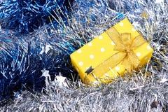 在发光的闪亮金属片背景的礼物盒 免版税库存图片