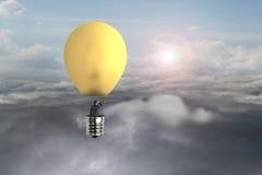 在发光的黄色电灯泡热空气气球飞行的商人 免版税库存图片