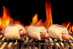 在发火焰BBQ格栅的三个热狗 免版税库存照片