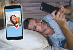 在发现美好的女孩外形的线搜寻性的或爱的床上的年轻可爱的人送象使用流动pho 免版税库存照片