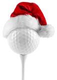 在发球区域圣诞老人帽子的高尔夫球 库存照片