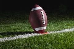 在发球区域的学院橄榄球在晚上准备好反撞力  免版税库存照片