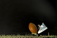 在发球区域的橄榄球与一双鞋子在黑背景中 库存照片