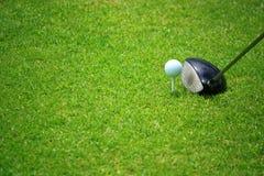 在发球区域的高尔夫球与司机和美丽的绿草 库存图片