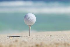 在发球区域的高尔夫球在与后边海浪的沙子海滩 免版税库存照片