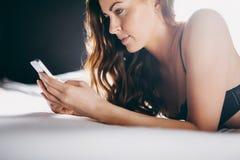 在发短信与她的手机的床上的美丽的少妇 免版税库存照片
