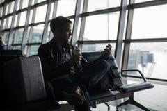 在发短信与他巧妙的电话的机场休息室供以人员等待 免版税库存照片