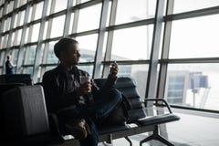 在发短信与他巧妙的电话的机场休息室供以人员等待 图库摄影