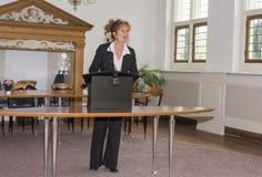 在发表讲话的书桌后的Busniss妇女 免版税库存照片