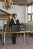 在发表讲话的书桌后的Busniss妇女 免版税图库摄影