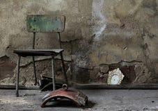 在发霉的墙壁上的老木椅子 免版税库存照片